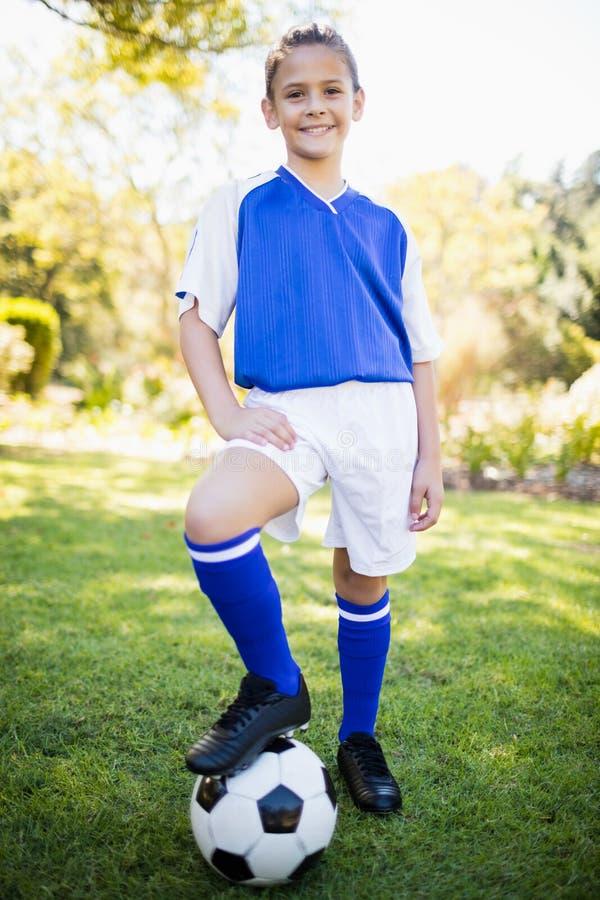 Vooraanzicht van meisje dat voetbal eenvormige status draagt stock foto