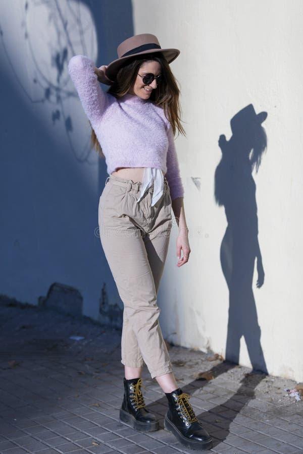 Vooraanzicht van mooie in jonge vrouw zonnebril dragen en hoed die zich in de straat bevinden terwijl het stellen aan camera in e royalty-vrije stock afbeeldingen