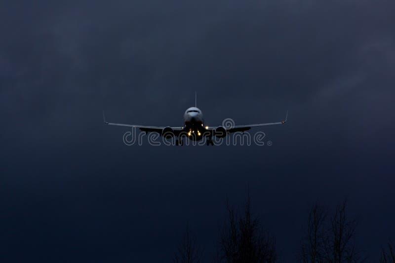 Vooraanzicht van passagiersvliegtuig die bij nacht landen royalty-vrije stock foto