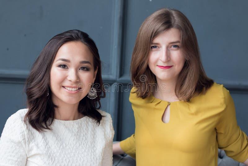 Vooraanzicht van twee glimlachende jonge vrouwelijke vrienden die in de woonkamer thuis zitten stock foto