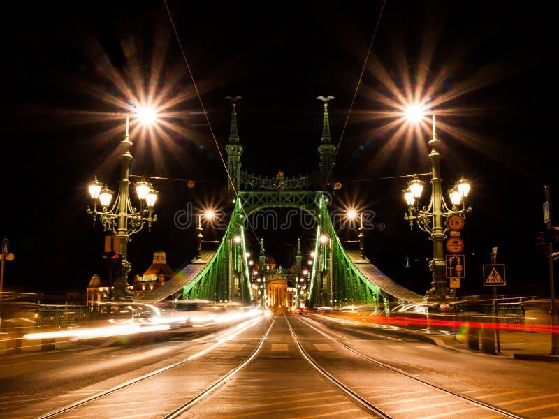 Vooraanzicht van verlichte Vrijheidsbrug in Boedapest, Hongarije Nacht geschotene lange blootstelling met autolichten royalty-vrije stock afbeelding