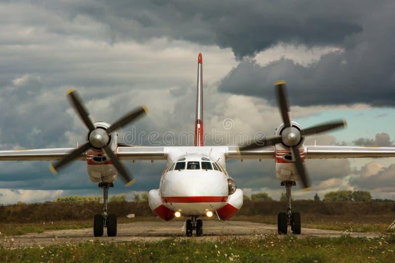 Vooraanzicht van vliegtuig met het draaien van propellers op onweersclou stock foto