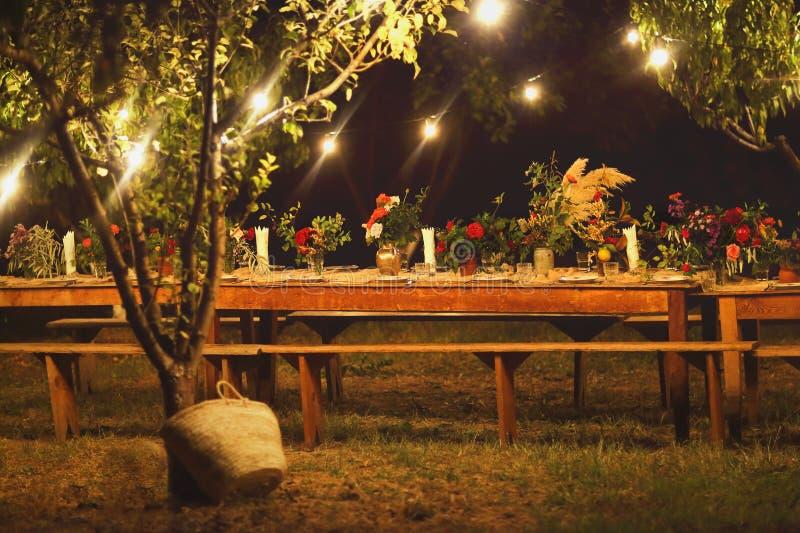 Voorbereide lijst voor een rustiek openluchtdiner bij nacht met winegla stock foto