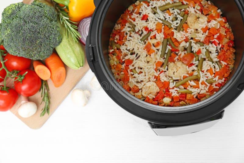 Voorbereide rijst met groenten in multikooktoestel op keukenlijst stock fotografie