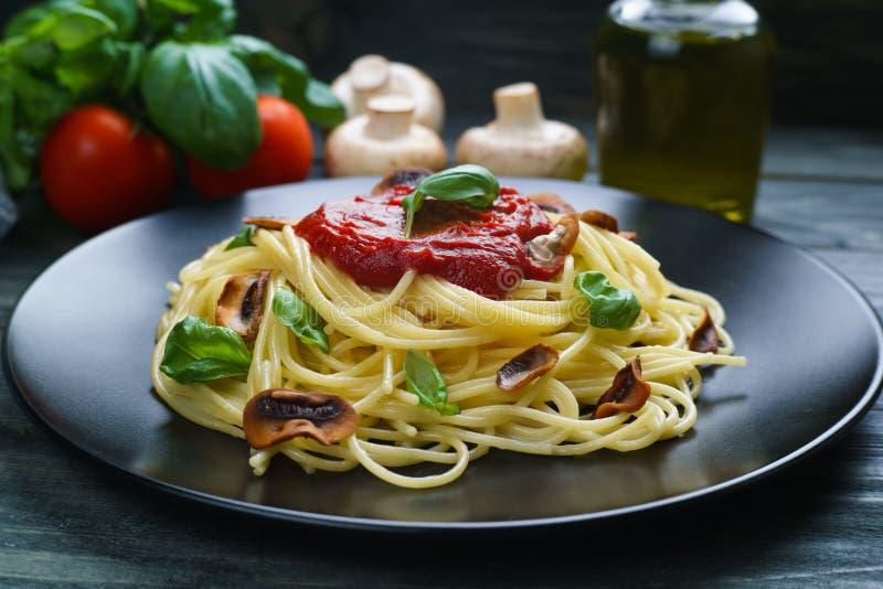 Voorbereide spaghettideegwaren met tomatensaus, geroosterde champignons stock afbeeldingen