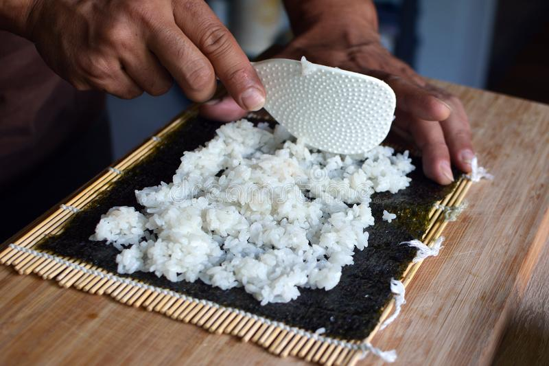 Voorbereidend eigengemaakte sushi door witte rijst op een droog blad van het norizeewier op bamboemat te zetten royalty-vrije stock afbeeldingen