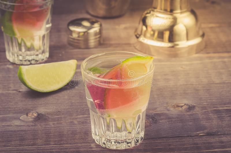voorbereiding van cocktail met een kalk in een schudbeker/voorbereiding van cocktail met een kalk in een schudbeker op een houten stock afbeeldingen