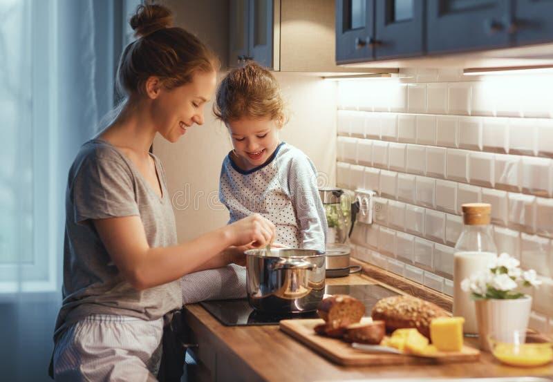 Voorbereiding van de moeder van het familieontbijt en de kok van de kinddochter stock fotografie