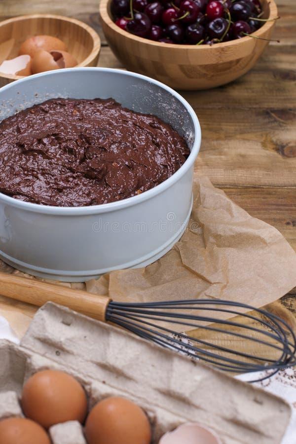 Voorbereiding van een chocoladecake met een kers Traditionele Amerikaanse cake Ingrediënten voor Baksel De ruimte van het exempla stock fotografie