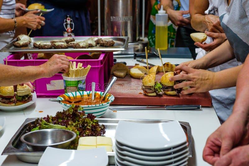 Voorbereiding van Hamburgers bij een hertevlees het koken gebeurtenis stock foto's