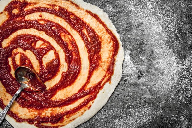 Voorbereiding van pizza Toepassing van tomatensaus op het gerolde deeg stock afbeeldingen