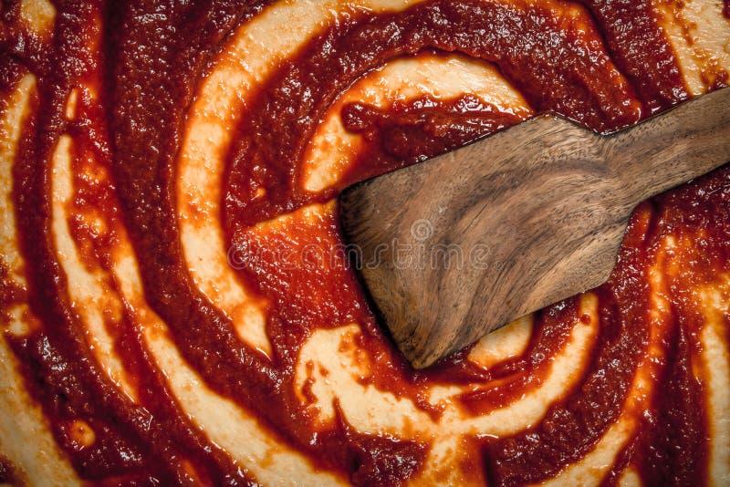 Voorbereiding van pizza Toepassing van tomatensaus op het gerolde deeg royalty-vrije stock foto
