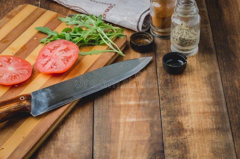 Voorbereiding van vegetarische salade Tomaten met arugula en kruiden Een mes en kruiden op een houten achtergrond De ruimte van h stock afbeelding
