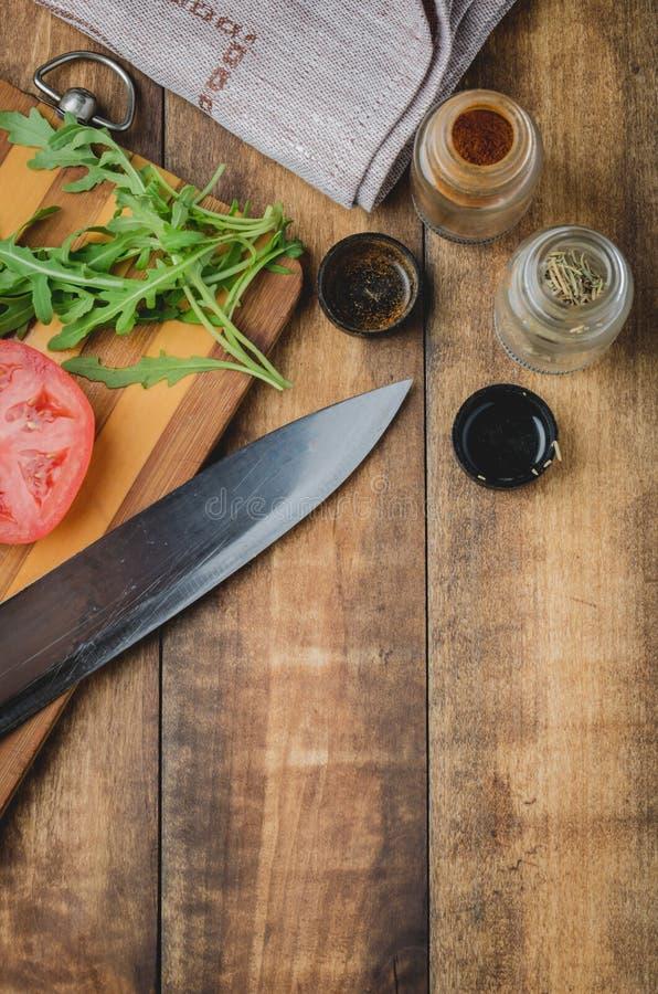 Voorbereiding van vegetarische salade Tomaten met arugula en kruiden Een mes en kruiden op een houten achtergrond Hoogste mening  royalty-vrije stock foto