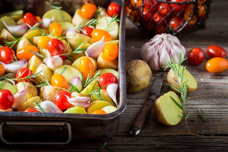 Voorbereiding voor geroosterde eigengemaakte aardappel met knoflook, rozemarijn en tomaten stock fotografie