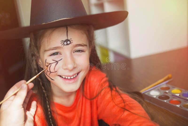 Voorbereiding voor Halloween kind in een heksenuitrusting die gezicht het schilderen doen Leuke Spin diy idee van eenvoudig kostu royalty-vrije stock foto's