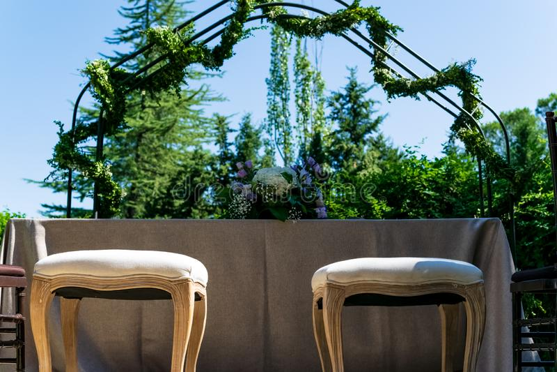 Voorbereidingen en decoratie vóór de ceremonie van een huwelijk waar er een boog en twee stoelen voor de bruid en de bruidegom zi stock fotografie