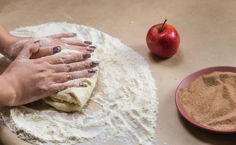 Voorbereidingskoekjes met kaneel, kwark en appelen op kraftpapier-document Vrouwelijke handen die deeg in maaltijd rollen stock fotografie