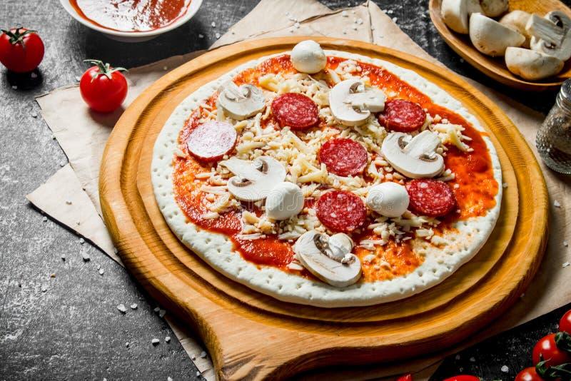 Voorbereidingspizza Ontwikkeld deeg met tomatenpuree, worsten, paddestoelen en kaas stock foto's