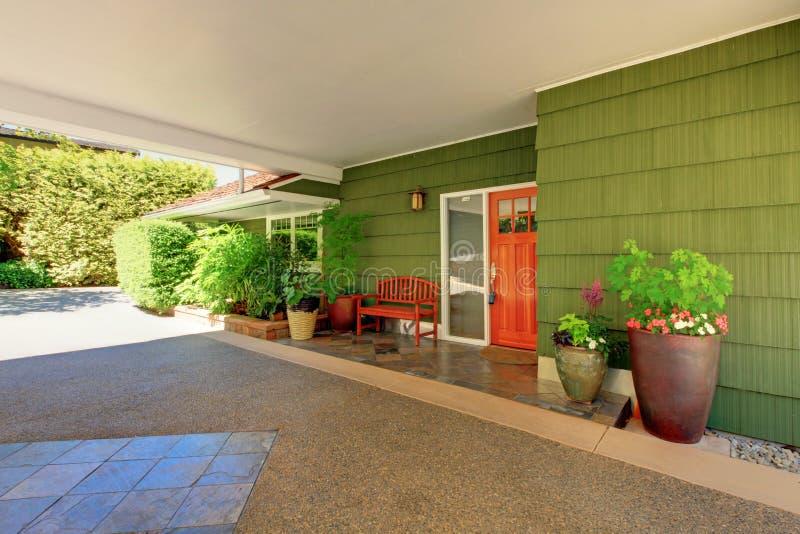 Voordeur en groen huis met aardig randberoep. stock fotografie