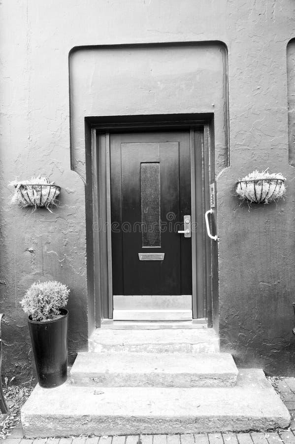Voordeur met stappen in reykjavik, IJsland Huisingang met rode deur en potteninstallatiedecoratie Privé-bezit en royalty-vrije stock fotografie