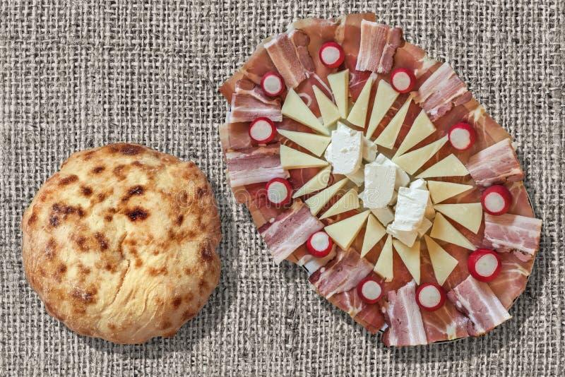 Voorgerecht het Smakelijke die Schotel en Brood van Flatbread Pitta op de Ruwe Gebleekte Oppervlakte van Grunge van het Jutecanva stock foto
