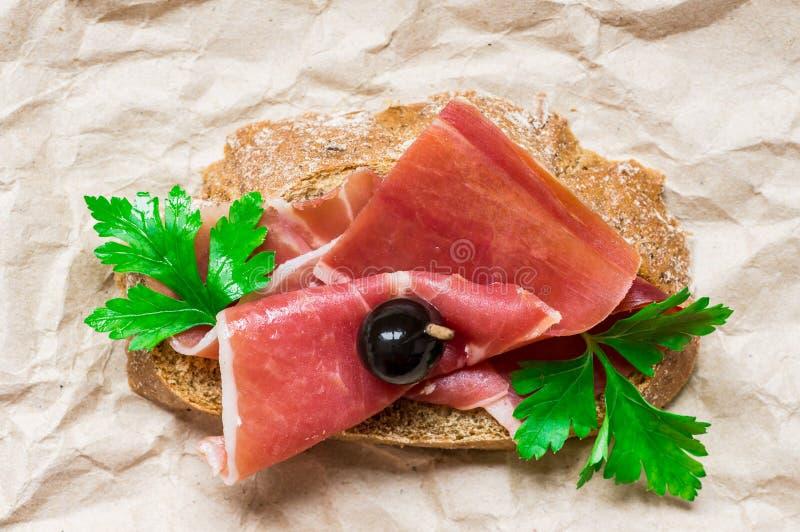 Voorgerecht met bacon, toost en olijven stock fotografie