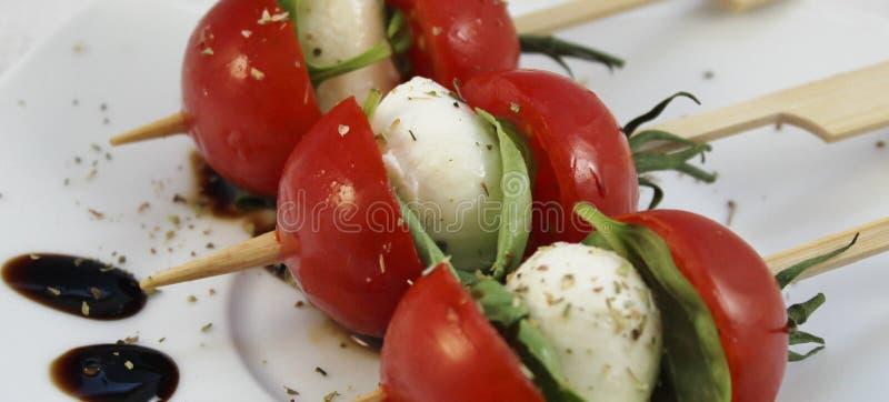 Voorgerecht met van de babymozarella en cocktail tomaten op vleespennen stock foto's