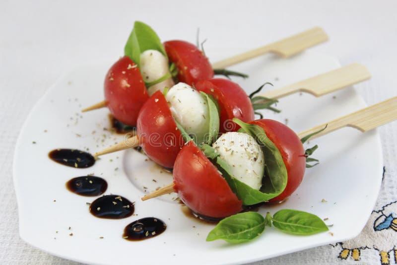 Voorgerecht met van de babymozarella en cocktail tomaten op vleespennen stock afbeeldingen