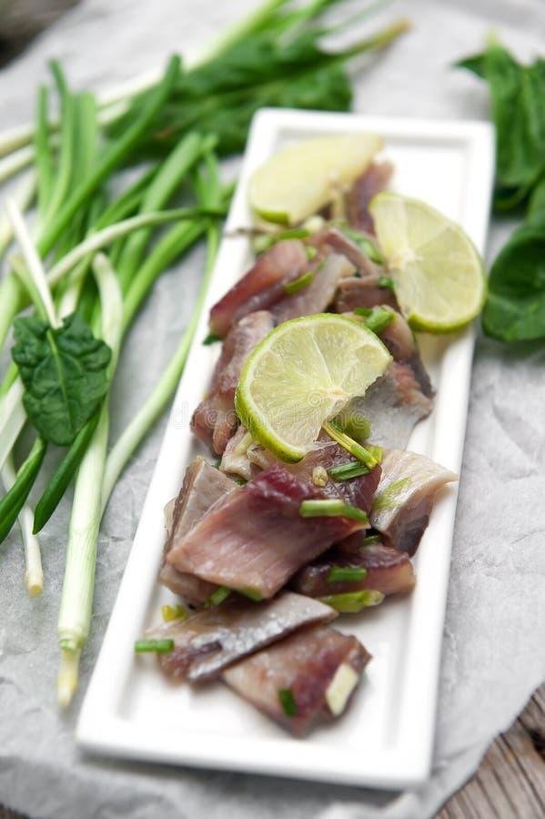 Voorgerecht van kruidige haringen met kalk en groene ui stock afbeeldingen