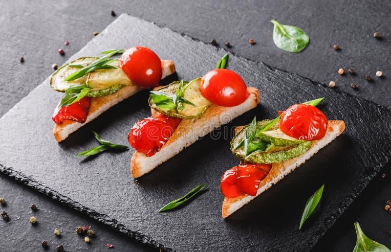 Voorgerechtbruschetta met groenten, de tomaten en de kruiden op zwarte schalie schepen over zwarte steenachtergrond in Gezond voe royalty-vrije stock afbeelding