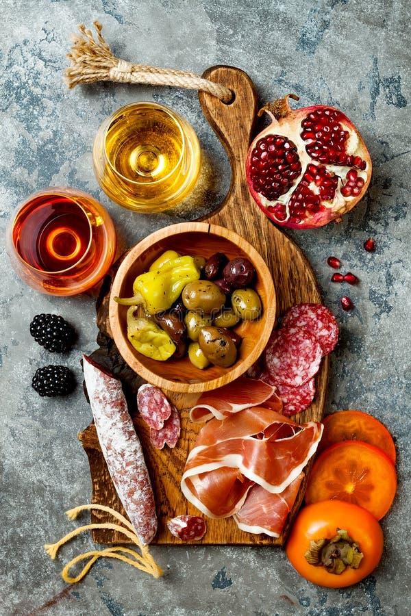 Voorgerechtenlijst met Italiaanse antipastisnacks en wijn in glazen Charcuterieraad over grijze concrete achtergrond Hoogste meni stock afbeeldingen