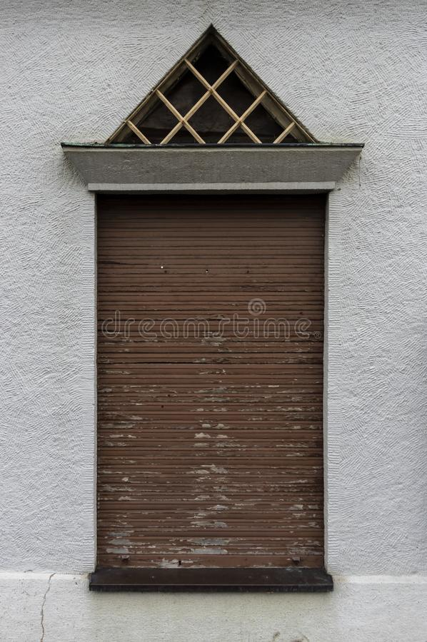 Voorgevel met hoge vensters en gesloten oude houten blinden, driehoekig dakraam met binnen traliewerk als inbrekerbescherming en  stock foto