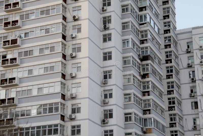 Voorgevel van de moderne woon hoge stijgingsbouw met veel vensters en flats stock afbeelding