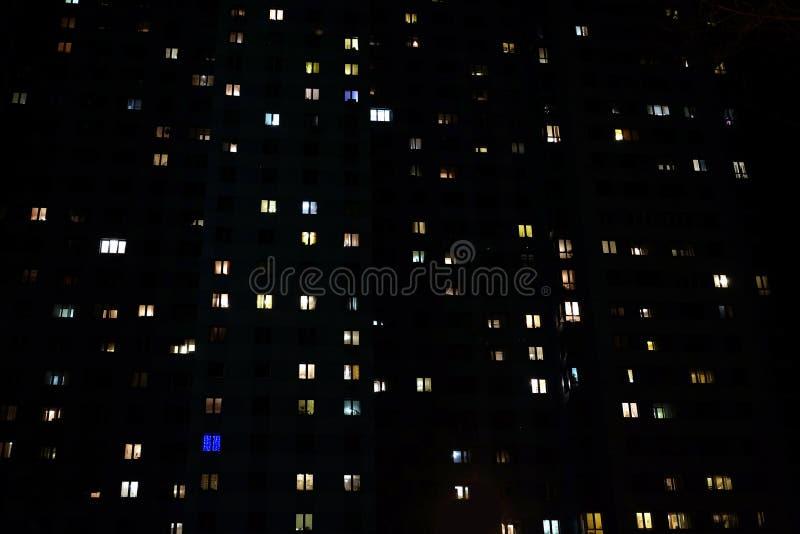 Voorgevel van een groot flatgebouw met meerdere verdiepingen met vele verlichtingsvensters in de mening van de flatsnacht royalty-vrije stock fotografie