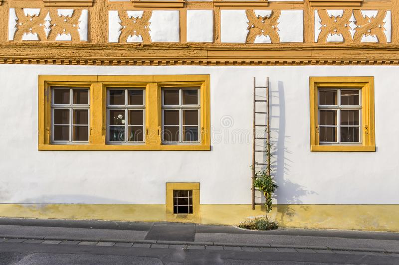 Voorgevel van een hersteld helft-betimmerd huis met gedetailleerde die ornamenten gedeeltelijk met oude houten ladder en bloemen  stock afbeelding