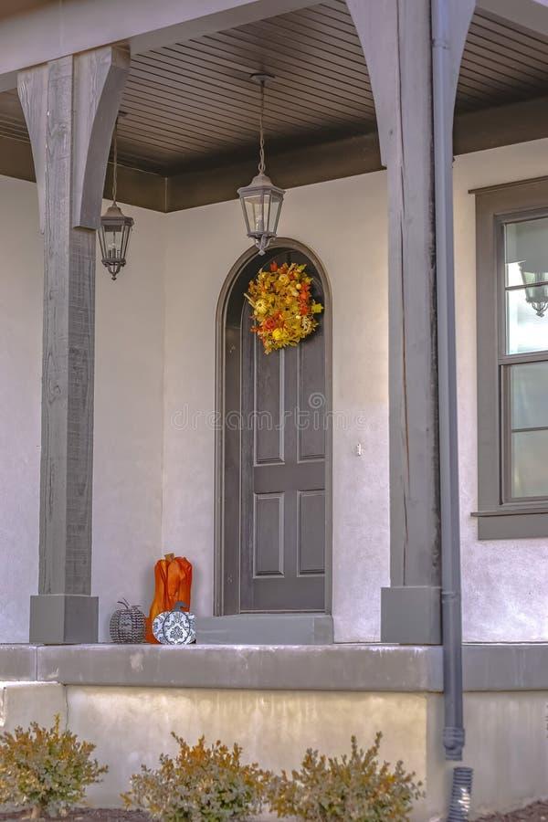 Voorgevel van een huis die een kleine voorportiek en een overspannen deur met kroon kenmerken stock foto's