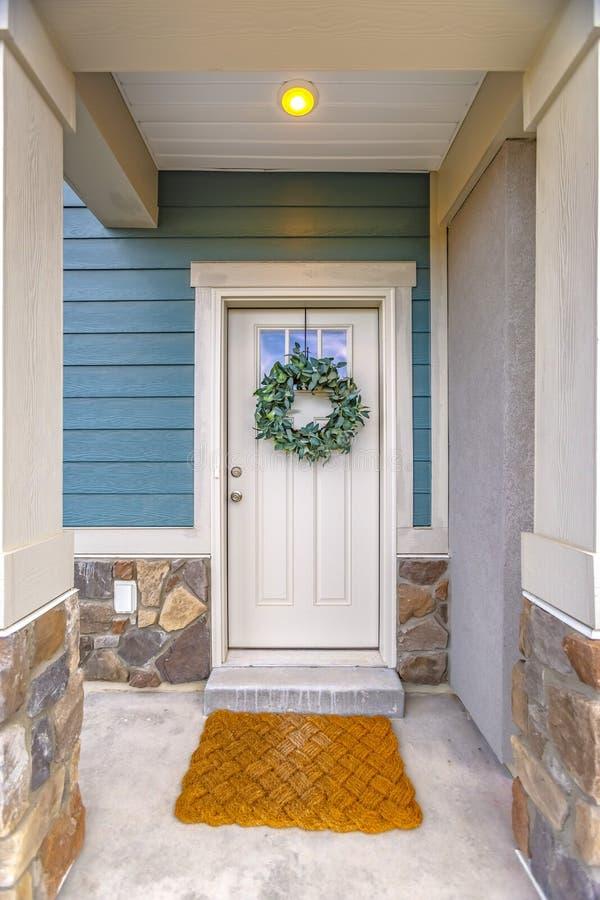 Voorgevel van een huis met een eenvoudige bladkroon die op de witte voordeur hangen stock foto
