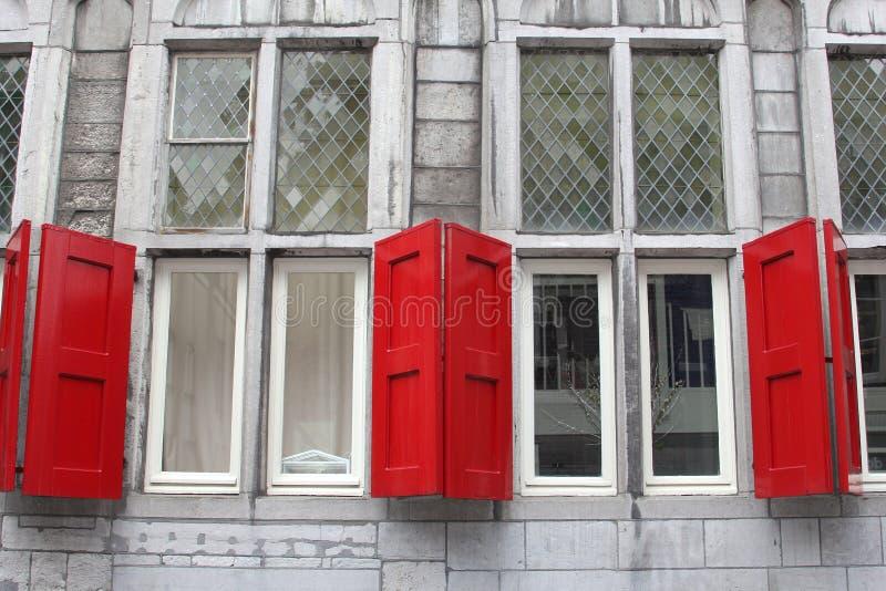 Voorgevel van een oud gebouw met rode schuilplaatsen en gebrandschilderd glasvensters, Utrecht, Nederland stock afbeelding