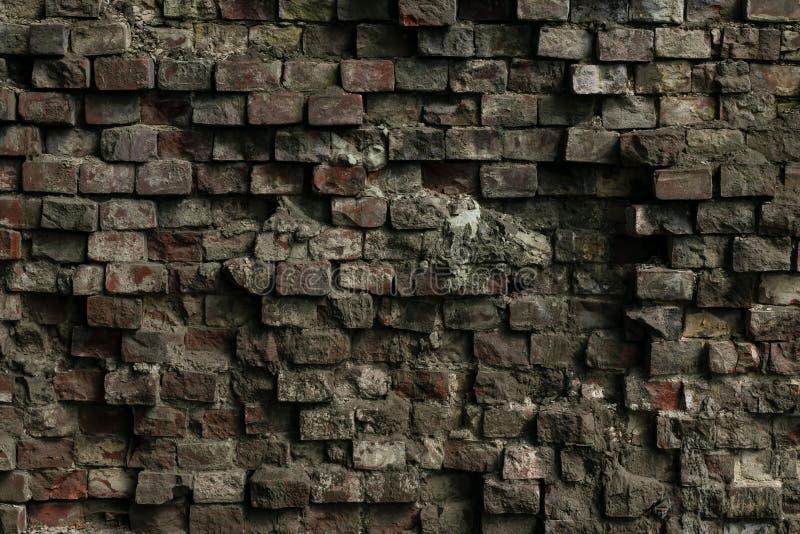 Voorgevel van een oud geruïneerd gebouw Textuur van een verbrijzelde grunge cementmuur De grijze vuile dilapidated bakstenen muur stock afbeeldingen