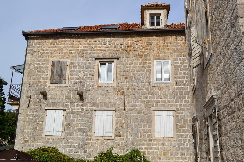 Voorgevel van een oud steenhuis met meerdere verdiepingen De vensters zijn behandeld met houten blinden Oude stad van Budva monte royalty-vrije stock afbeeldingen