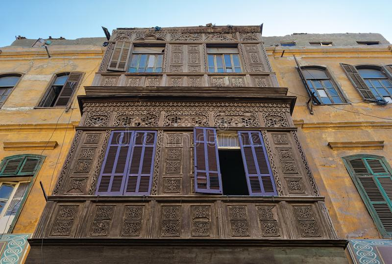 Voorgevel van een oude woningbouw met houten overladen gegraveerde muur, gele geschilderde muur, en viooltje geschilderde houten  stock foto's