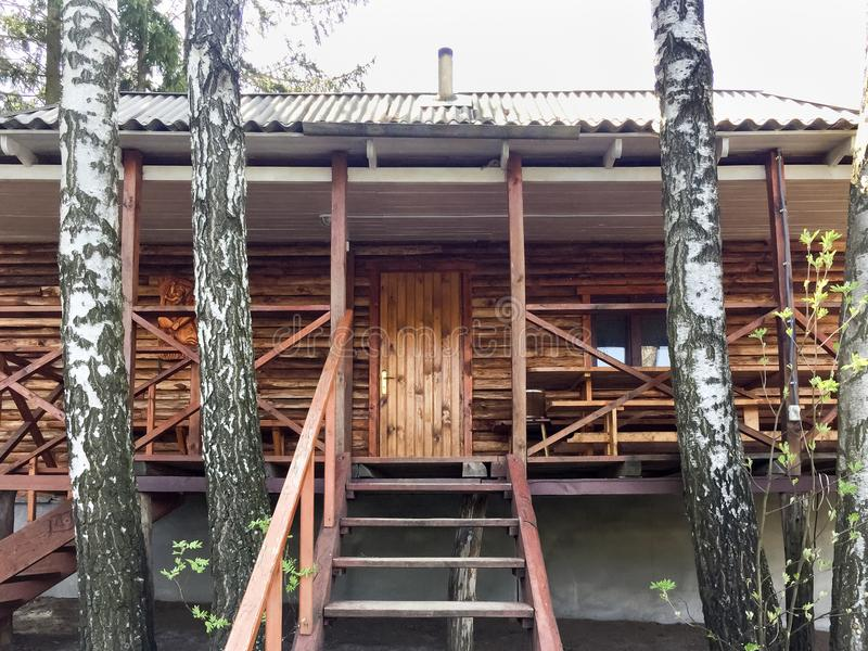 Voorgevel van houten de zomerplattelandshuisje in de schaduw van bomen royalty-vrije stock foto's