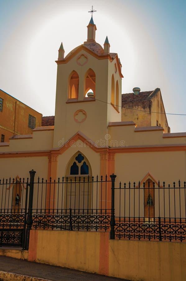 Voorgevel van kleine kerk en klokketoren, achter ijzeromheining, met zonneschijn erachter bij zonsondergang in São Manuel royalty-vrije stock afbeelding