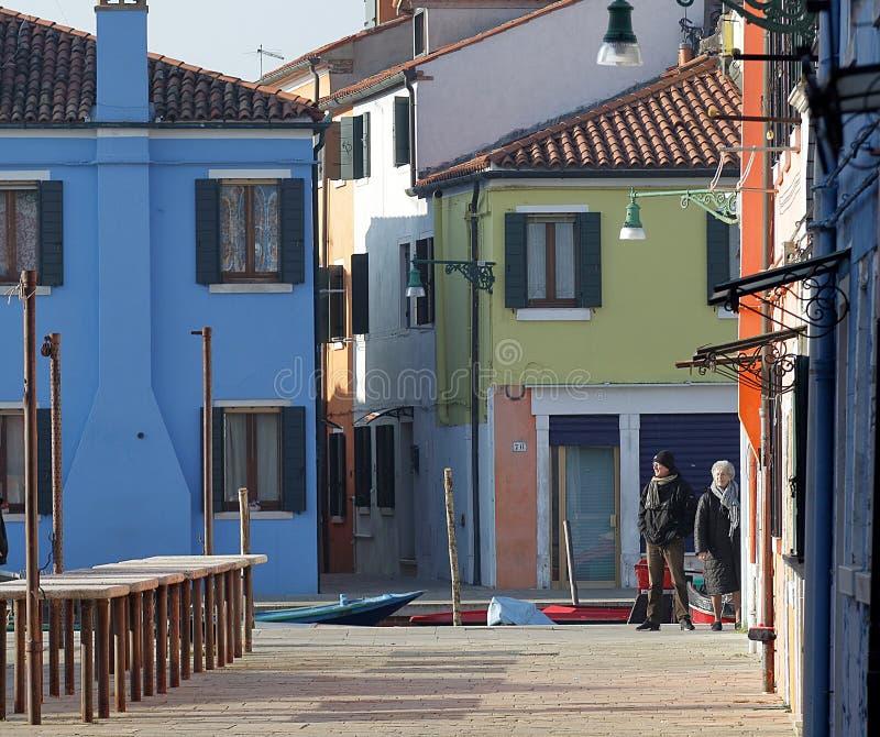Voorgevels van kleurrijke gebouwen en toeristen die in de stad van Burano, Italië lopen royalty-vrije stock fotografie