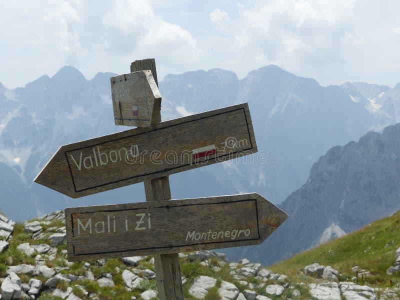 Voorgrond van houten pijlen met geschrift als aanwijzingen van berg albanië stock foto
