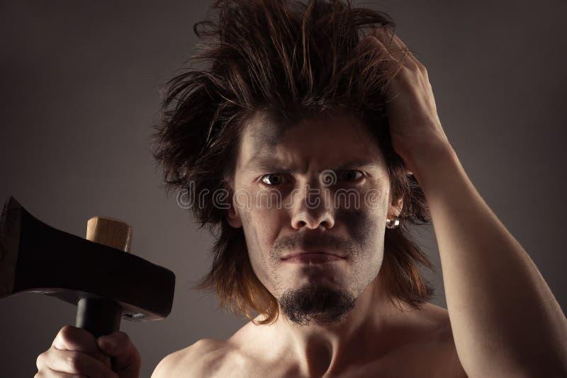 Voorhistorische mens met een in hand bijl stock afbeeldingen