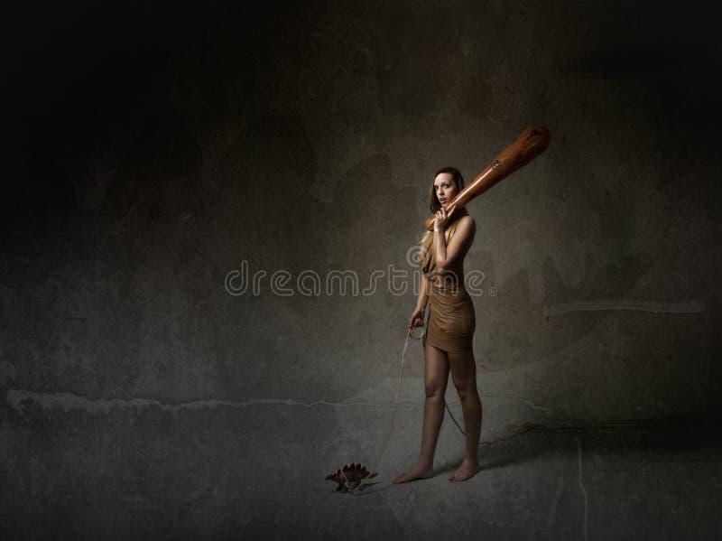 Voorhistorische vrouw met huisdier en club stock fotografie