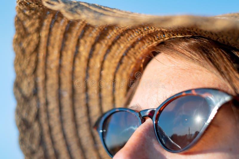 Voorhoofd van een vrouw met sproeten in direct zonlicht, close-upmening stock foto