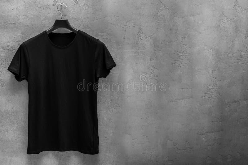 Voorkant van mannelijke zwarte katoenen t-shirt op een hanger en een concrete muur op de achtergrond stock foto's